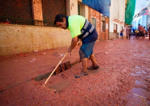 A worker cleans a street covered in tomatoes after La Tomatina in Spain