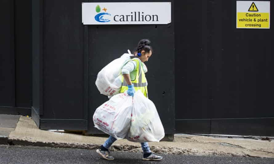 a cleaner passes a Carillion site sign