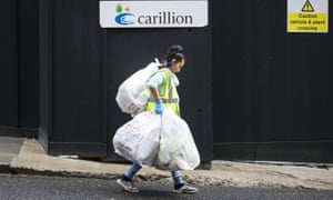 Rubbish bags are carried away from a closed Carillion construction site