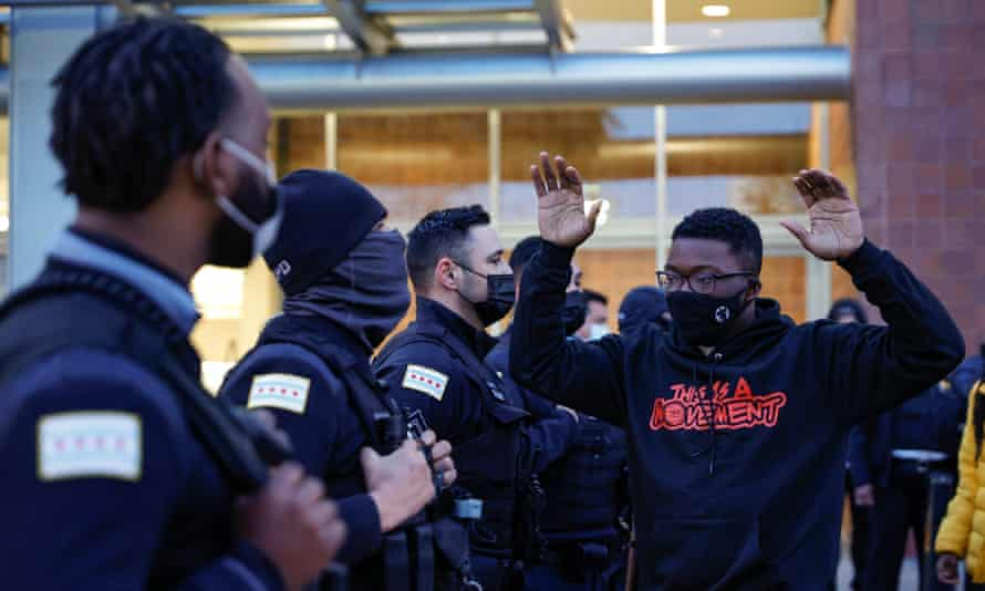 An activist holds his hands up outside Chicago police headquarters during a rally on 15 April.