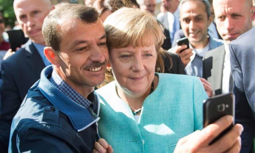 An asylum seeker takes a selfie with the German chancellor, Angela Merkel, in 2015.