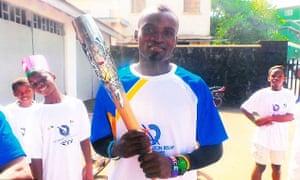 Jimmy Thoronka holds the Commonwealth Games baton in Sierra Leone.