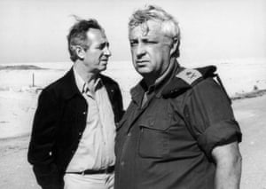Peres and a man in military uniform standing looking in different directions