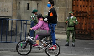 A woman wears a protective mask as she rides a bicycle in Mexico City, Mexico, 10 May 2020.
