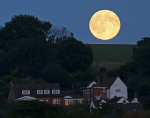 The blue moon rises over the brow of a hill