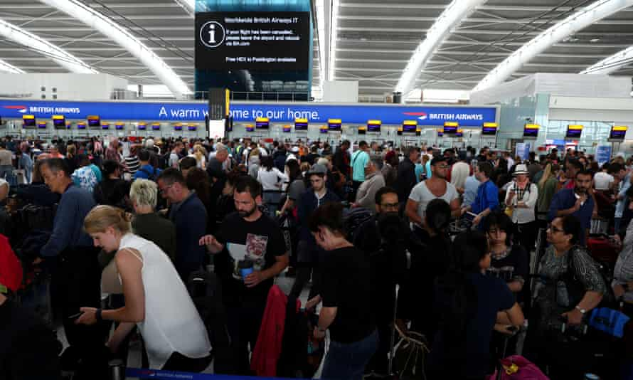 People wait with their luggage at the British Airways check-in desks at Heathrow Terminal 5 on Sunday.