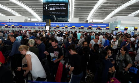 People wait with their luggage at Heathrow Terminal 5 in London.