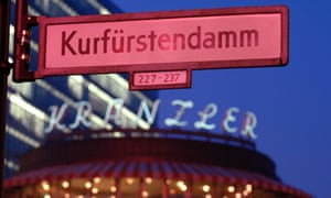 Sign reading Kurfürstendamm above a shop on a street in Berlin.
