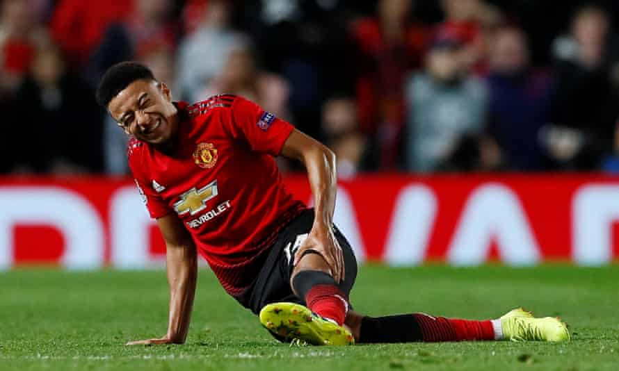Manchester United's Jesse Lingard holds his leg after suffering the injury against PSG