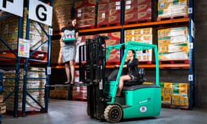 Iseult Ward standing on a forklift truck and Aoibheann O'Brien driving it in the FoodCloud warehouse in Dublin.