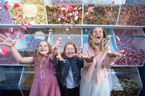 London, UK(L-R) Daisie Burt, Ruby Cohen and Mia Nijs enjoy free sweets from a giant five metre tall pick 'n' mix display, which has been unveiled on London's Southbank