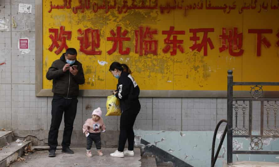 A family stands at the entrance to an underground retail street in Aksu in western China's Xinjiang region