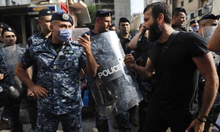 An anti-government protester shouts at riot police in Beirut on Friday, near the scene where a Lebanese man killed himself apparently because of the deteriorating economic and financial crisis.