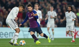 Lionel Messi of Barcelona tussles with Raphael Varane of Real Madrid.
