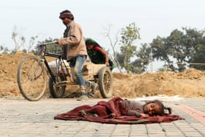 New Delhi, India: people push a tricycle while a child rests on a blanket nearby
