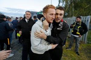MK Dons club captain Dean Lewington is hugged by MK fans as he gets off the team coach
