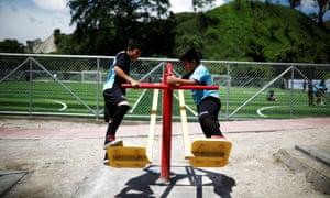 Children play at a new sports complex at La Campanera neighborhood in Soyapango, El Salvador
