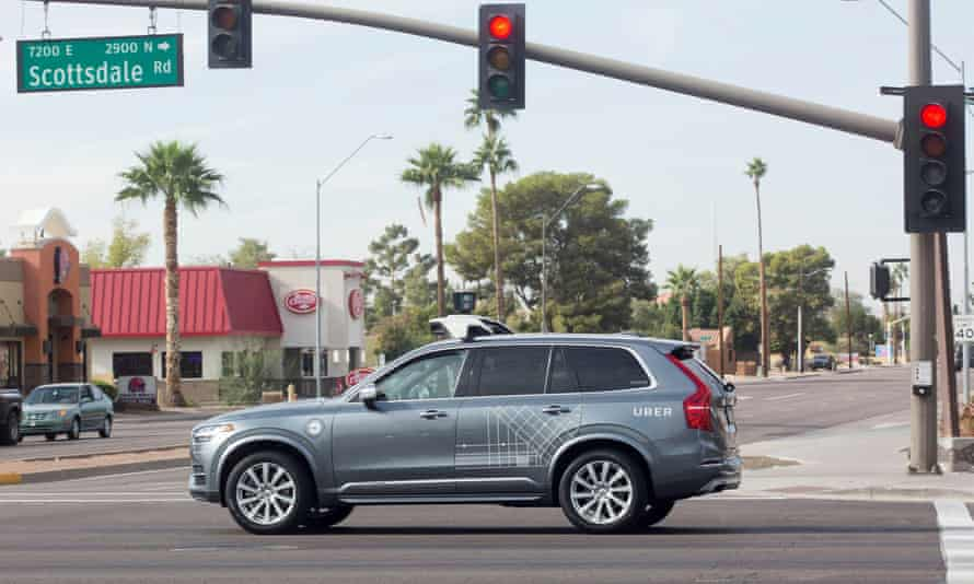 An Uber self-driving vehicle drives through an intersection in Scottsdale, Arizona.