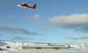 Lots of blue sky; a low horizon is a strip of white snow and low single storey grey huts.  Top right a bright red and white biplane has just taken off.