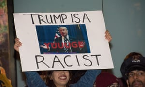 A protester holds a sign at a rally against Donald Trump hosting Saturday Night Live.