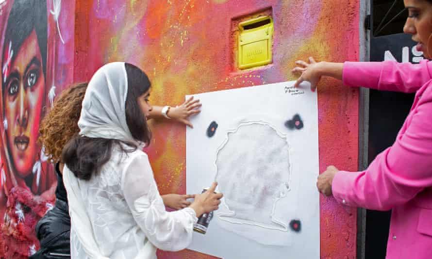 Malala Yousafzai helps stencil a graffiti design of Marielle Franco on the wall of a Rio favela.