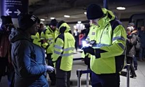 A worker checks a passenger's ID