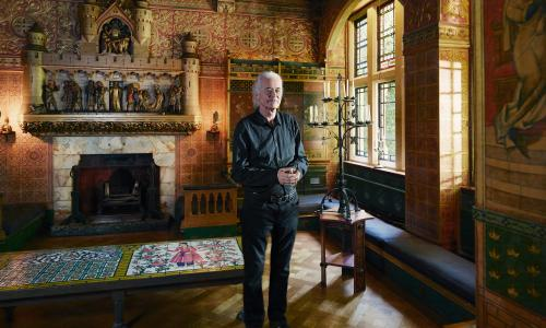Jimmy Pages standing in the library of his home with its ornate fireplace and highly decorated walls