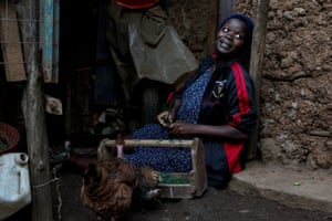 Bosibori, now nine-months pregnant, sits outside her home with her family's hen.