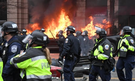 Police officers move protesters away from a car that was set on fire during protests near the inauguration of Donald Trump in Washington.