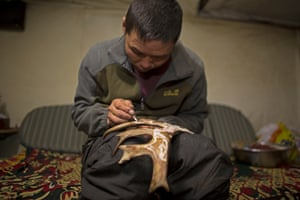 Oltsen decorates a piece of reindeer antler – the Dukha can make money from selling craftwork to tourists.
