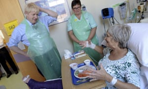 Boris Johnson speaking to patient Wenona Pappin, 70, during a visit to Torbay Hospital, south England, this afternoon.