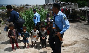 Pakistani policemen escort members of a polio vaccination team during a door-to-door polio immunisation campaign on the outskirts of Islamabad