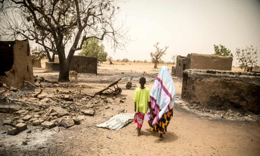 Maïmouna Barry, 45, walks through what is left of the village of Ogossagou-Peulh in Mali, following a recent attack, with her daughter Hawa, 10