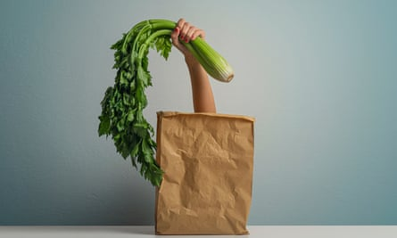 Woman' hand with celery comes out of a Paper Bag