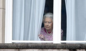 The Queen peers out of a window of Buckingham Palace