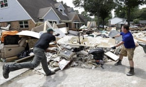 Volunteers Travis Adair, right, and Matt Vinks, throw a kitchen sink damaged by floodwaters onto a pile of debris in the aftermath of Harvey.