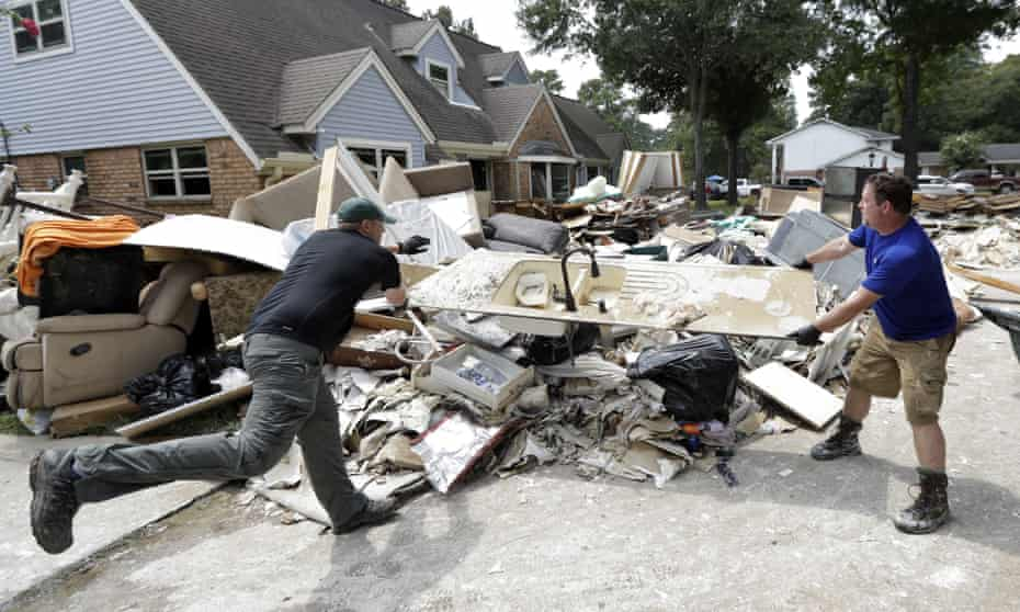 Volunteers Travis Adair, right, and Matt Vinks throw a kitchen sink damaged by flood waters on to a pile of debris.