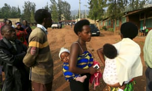 Mothers carrying their babies wait to vote in a referendum on amending the nation's constitution to allow president Paul Kagame to seek a third term.
