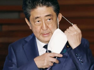Japan's prime minister, Shinzo Abe, takes off his mask to speak to the media at his official residence in Tokyo