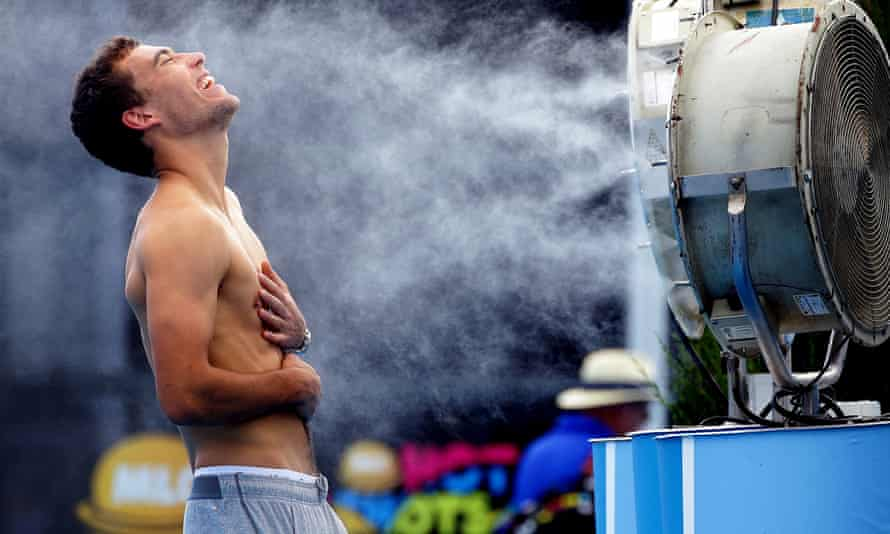 Poland's Jerry Janowicz is sprayed with cool water at the Australian Open tennis championship in Melbourne, Australia in 2014.