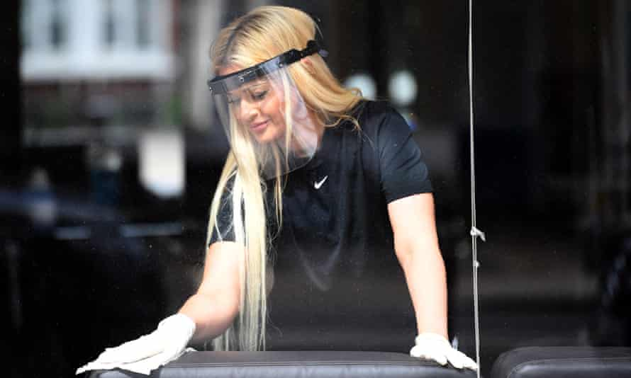Stephanie Chrysostomou wears PPE as she cleans her beauty salon, Imagination, in north London on Friday.