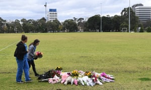 Two women lay flowers at a growing makeshift memorial for Eurydice Dixon at the Princes Park sporting precinct, Melbourne.