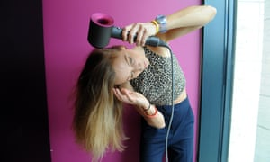 A woman uses the Dyson Demo hairdryer