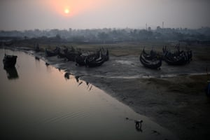 A Rohingya refugee works in the water at dawn beside fishing boats in Shamlapur refugee camp