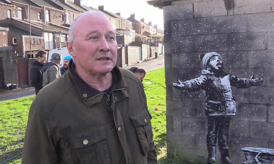 Man standing in front of a Banksy