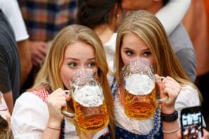 Girls in traditional Bavarian dress enjoy the beer
