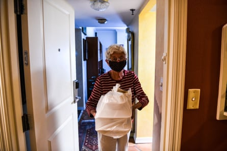 Charlie Aron, 84, wears a mask as she receives her food delivery in John Knox Village on 7 August. About 900 retirees live in the South Florida senior community.