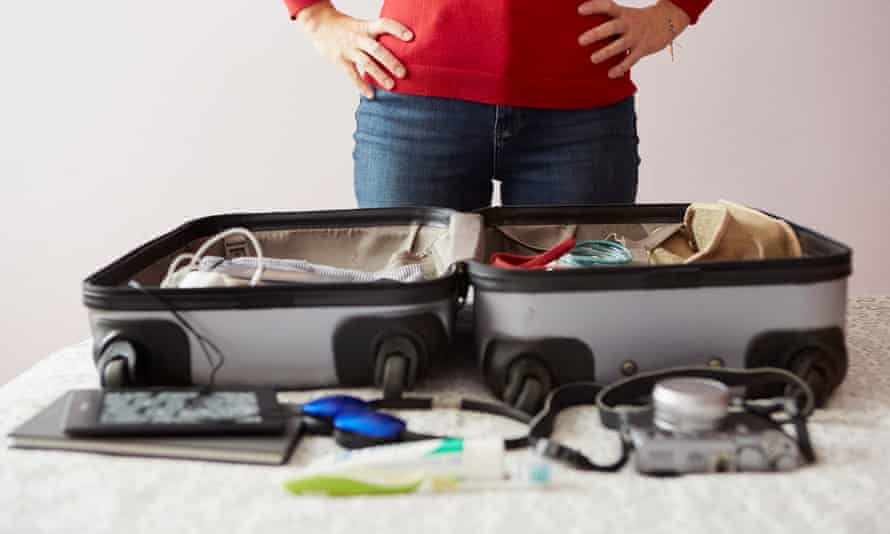 Woman packing suitcase, hands on hips.
