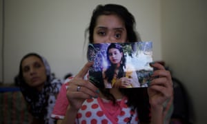 Shakila shows a picture of herself before she was shot by her husband.