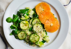 fregola, cucumber and orange salad on a round plate